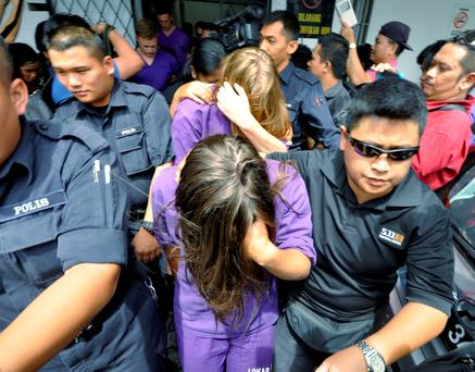 British national Eleanor Hawkins (front), along with three other tourists from Canada and the Netherlands, are escorted by police as they leave a court hearing in Kota Kinabalu, in Malaysia's eastern state of Sabah June 10, 2015. REUTERS/New Straits Times/Mohd Adam Arinin