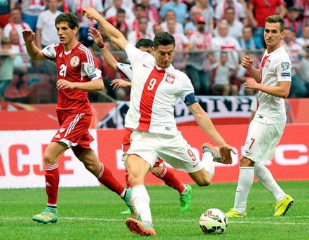 Poland's Robert Lewandowski scores a goal next to Georgia's Arkadiusz Milik (R) and Georgia's Lasha Dvali during the Euro 2016 Group D qualifying football match