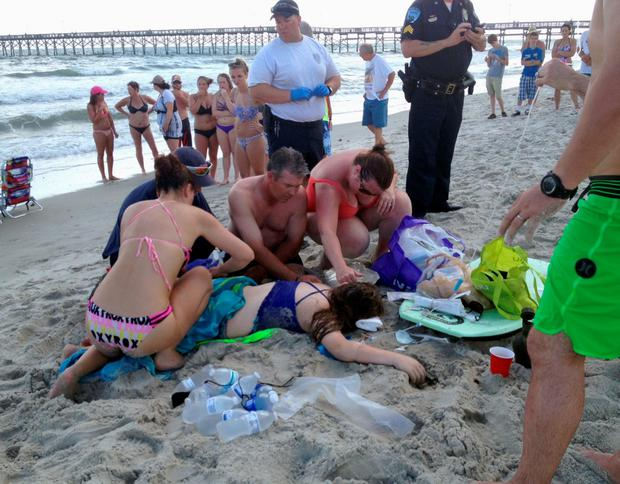 Emergency responders assist a teenage girl at the scene of a shark attack in Oak Island, N.C., Sunday, June 14, 2015. (Steve Bouser/The Pilot, Southern Pines, N.C. via AP)