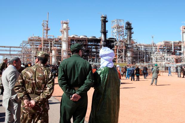Algerian soldiers and officials stand in front of the gas plant in Ain Amenas, seen in background, during a visit organized by the Algerian authorities for news media. (AP Photo, File)