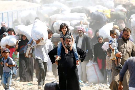 Syrian refugees carry their belongings as they cross into Turkey Credit: Umit Bektas