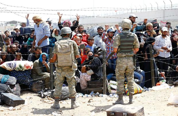 Turkish soldiers stand guard as Syrian refugees wait behind the border fences to cross into Turkey Credit: Umit Bektas