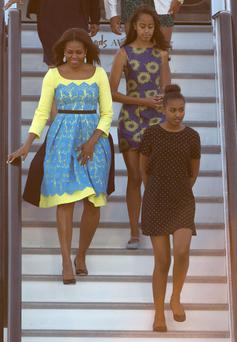 U.S. first lady Michelle Obama (L) and her daughters Malia (C) and Sasha (R) arrive at Stansted Airport, southern England June 15, 2015. REUTERS/Neil Hall