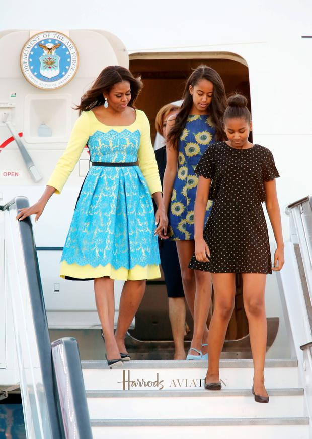 US first lady Michelle Obama accompanied by her daughters, Malia and Sasha (front), as she arrives at Stansted Airport, Essex, for a visit to the UK