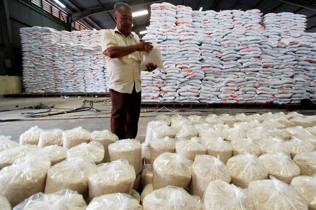 An government officer checks a sack of rice at the Bulog warehouse in Medan, Indonesia's South Sumatra province, June 15, 2015 in this photo taken by Antara Foto. Picture taken June 15, 2015. REUTERS/Antara Foto/Septianda Perdana