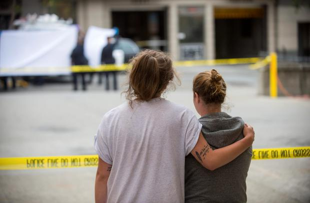 Two students embrace while watching the removal of a body of one of the deceased. Photo: AP