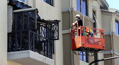 Workmen examine the damage at the scene of the balcony collapse in Berkeley, California