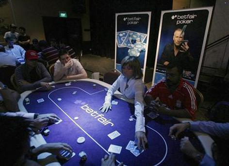 A dealer distributes cards at the Betfair Asian Poker Tour in Singapore November 12, 2006. REUTERS/Nicky Loh