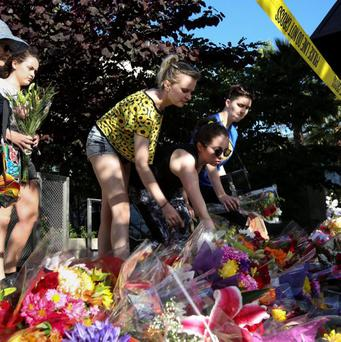 Visitors lay flowers on a makeshift memorial near the scene of a 4th-story apartment building balcony collapse in Berkeley, California June 16, 2015. REUTERS/Elijah Nouvelage