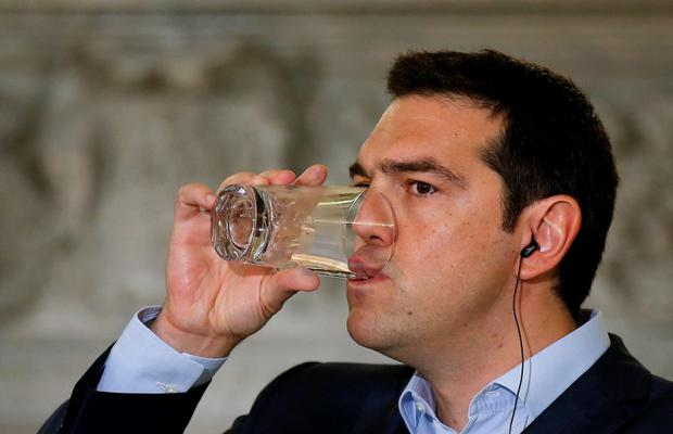 Greek Prime Minister Alexis Tsipras takes a drink during a news conference with Austrian Chancellor Werner Faymann at Maximos Mansion in Athens June 17, 2015. REUTERS/Paul Hanna