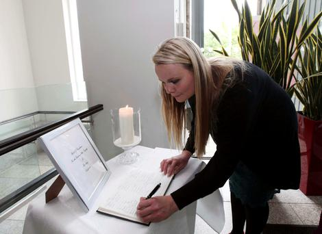 Labhaoise Murphy signs a book of condolences for the Berkeley victims in Dún Laoghaire Town Hall yesterday. Photo: Collins