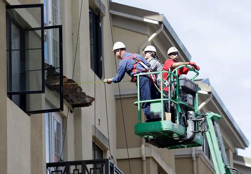 A worker measures near the remaining wood from the apartment building balcony that collapsed in Berkeley