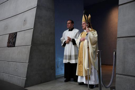 Two men participate in a special Mass for the victims of the Berkeley balcony collapse in Oakland, California June 17, 2015. REUTERS/Elijah Nouvelage