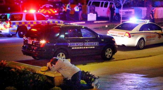 A man kneels across the street from where police gather outside the Emanuel AME Church following a shooting Wednesday, June 17, 2015, in Charleston, S.C. (Wade Spees/The Post And Courier via AP)