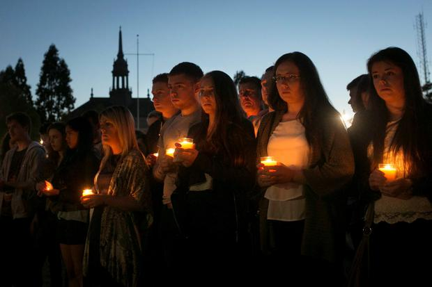 People hold candles during a candlelight vigil for the victims of the Berkeley balcony collapse in Berkeley, California, June 17, 2015. Three men and three women in their early 20s, including an American friend of the Irish students, died in the collapse, and seven others were hospitalized. REUTERS/Elijah Nouvelage
