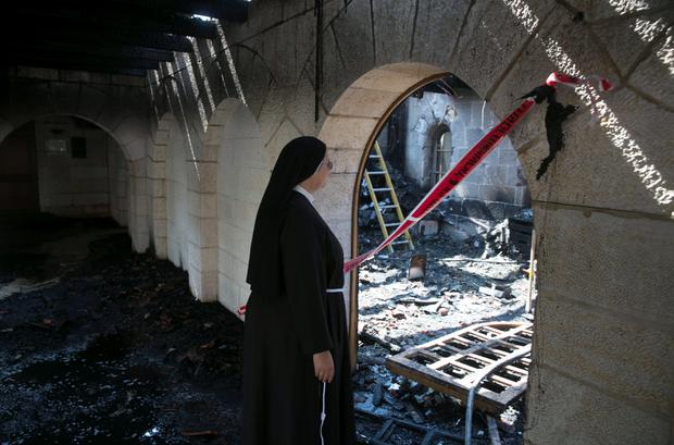 A nun looks at damage caused by a fire Credit: Baz Ratner