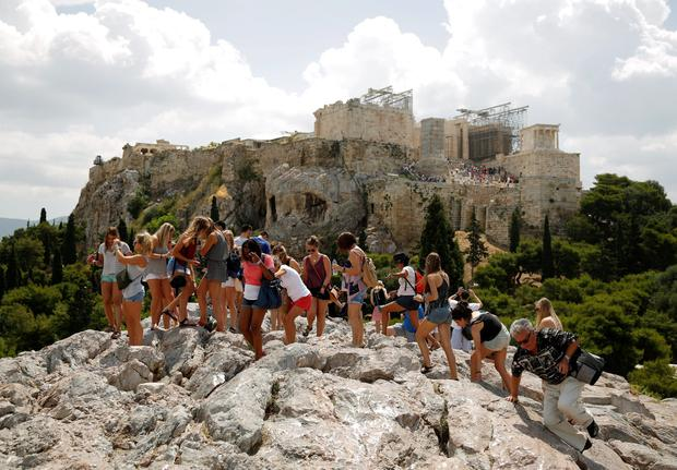 Tourists climb on a rock near the Acropolis hill in Athens June 18, 2015. Hopes of a breakthrough at Thursday's gathering of European finance ministers, once seen as the last opportunity for an agreement, looked increasingly remote. REUTERS/Paul Hanna