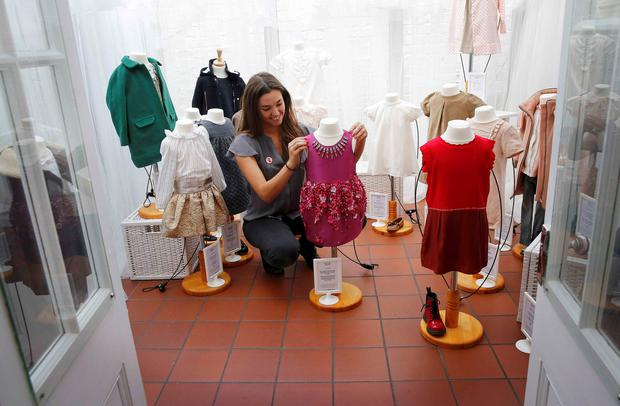 A employee poses with a pink Mischka Aoki dress which retails at GB Pounds 3,695, donated by Victoria Beckham and previously worn by her daughter Harper Beckham, at Mary's Living & Giving shop in the Primrose Hill neighbourhood of London, Britain June 16, 2015