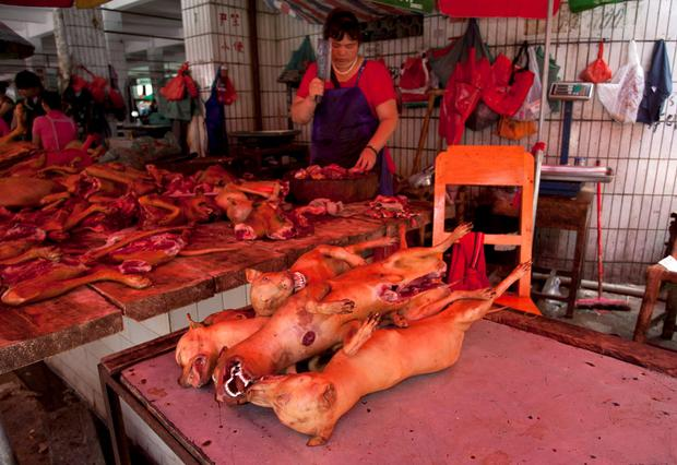 A vendor cuts butchered dogs at a dog meat market in Yulin ahead of a local Dog Meat Festival REUTERS/Stringer CHINA OUT