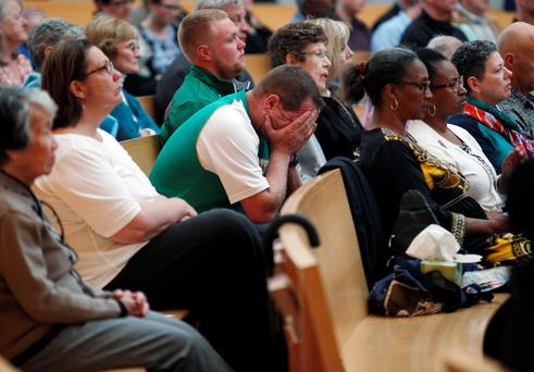 A man holds his head during a memorial service for six Irish students at the Cathedral of Christ in Oakland, Calif