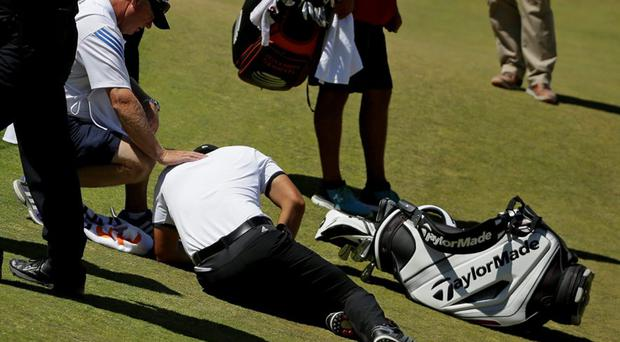 Jason Day lies in the fairway after falling down as his caddie Colin Swatton crouches beside him on the ninth hole during the second round of the U.S. Open golf tournament at Chambers Bay