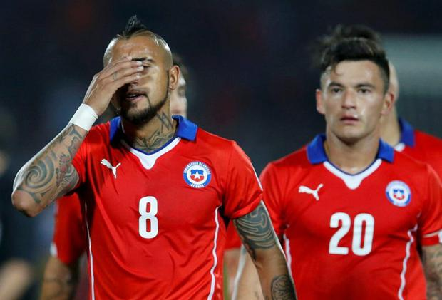 Chile's Arturo Vidal (8) and Charles Aranguiz leave the pitch at half-time during their first round Copa America 2015 soccer match against Boliovia at the National Stadium in Santiago