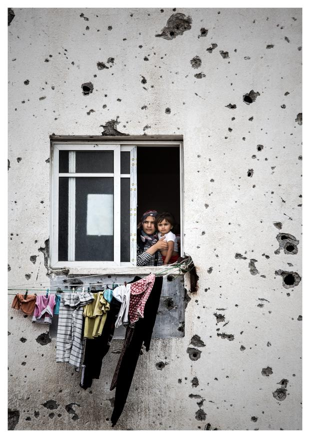 A mother hold her child while looking out from her Gaza City apartment which has been badly damaged from artillary fire and is unstable. Photo: Mark Condren