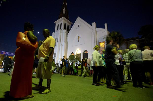 People stand outside during a vigil outside Emanuel African Methodist Episcopal Church in Charleston, June 20, 2015. Reuters/Carlo Allegri