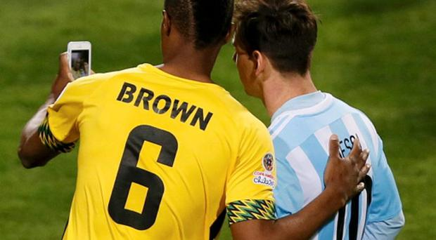 Jamaica's DeShorn Brown takes a selfie with Argentina's Lionel Messi