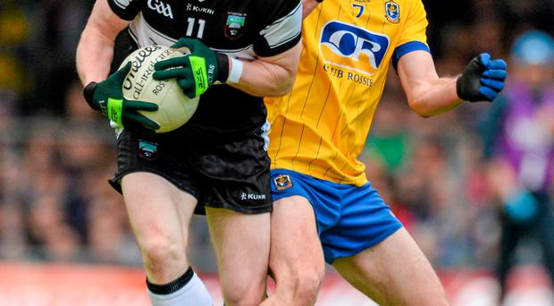 No quarter is asked or given as Sligo forward Mark Breheny holds off the challenge of Roscommon's Ciaran Cafferky