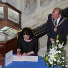 Lord Mayor Arder Carson and Secretary of State Teresa Villiers sign a book of condolence at Belfast City Hall after they opened a book of condolence for the Berkeley victims