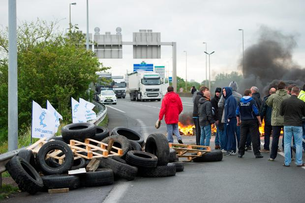 Striking ferry workers burn tyres as they block a ramp leading into the Eurotunnel before being dispersed by riot police in Calais