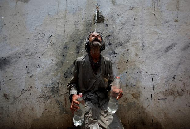 A man cools off from a public tap after filling bottles in Karachi Credit: Akhtar Soomro