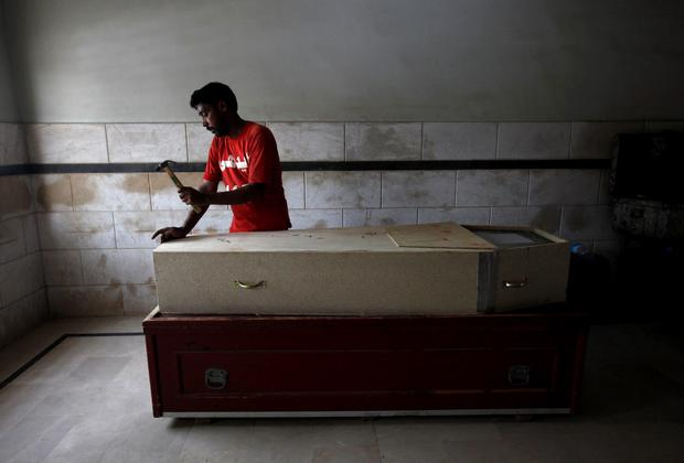 A volunteer prepares a coffin in Karachi for one of the 622 people killed due to an intense heat wave Credit: Akhtar Soomro