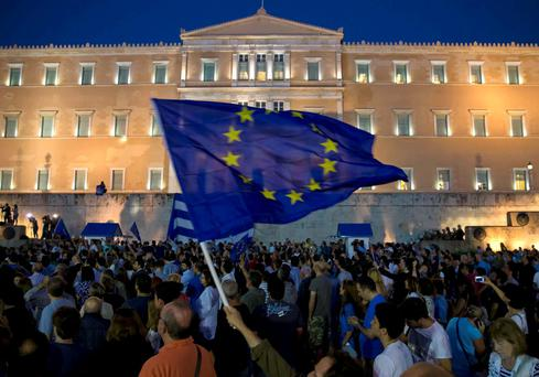 A protester waves a European Union flag in front of the parliament building during a rally calling on the government to clinch a deal with its international creditors and secure Greece's future in the Eurozone, in Athens. Photo: Reuters