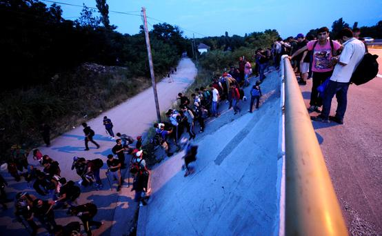 Migrants from Syria heading towards Hungary climb down a motorway near the Serbian border with Macedonia Credit: Ognen Teofilovski
