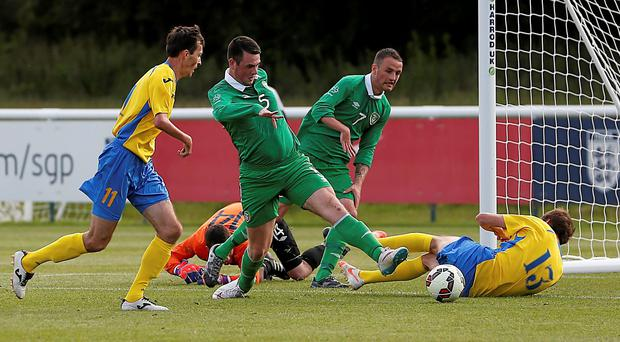 Eric O'Flaherty clears the ball after goalkeeper Simon Lestrange clashed with Ukraine's Artem Krasylnykov, resulting in a head injury