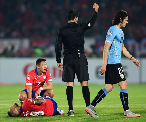 Uruguay's forward Edinson Cavani (R) leaves as Chile's midfielder Arturo Vidal (L, bottom) lies on the field next to teammate Chile's forward Alexis Sanchez during their 2015 Copa America football championship quarterfinal match, in Santiago, on June 24, 2015. AFP PHOTO / MARTIN BERNETTIMARTIN BERNETTI/AFP/Getty Images