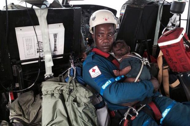 A rescue worker holding an infant rescued after five days in the jungle Credit: Getty Images