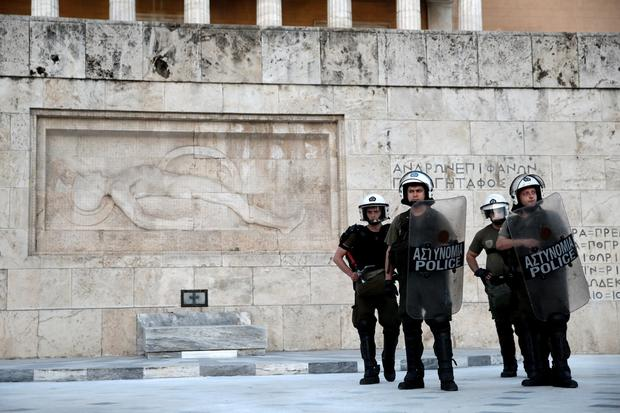 Riot policemen stand guard in front of the Tomb of the Unknown Soldier during an anti-bailout demonstration in Athens, Greece June 25, 2015. EU leaders discussed Greece's debt crisis with Prime Minister Alexis Tsipras for some two hours on Thursday in an unscheduled addition to their regular summit but insisted that negotiations be run by finance ministers, an EU official said. REUTERS/Alkis Konstantinidis