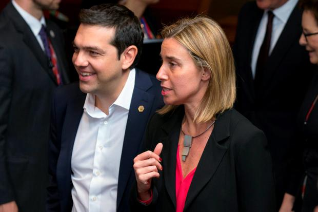 Greece's Prime Minister Alexis Tsipras (L) speaks with European Union Foreign Policy Chief Federica Mogherini as they arrives for a family photo at the EU Council headquarters during a European Union leaders summit in Brussels, Belgium, June 25, 2015. REUTERS/Philippe Wojazer