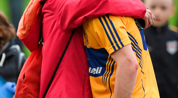Clare's Colm Fitzgerald is comforted by his mother Ciara Flynn after the game at Semple Stadium