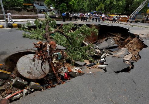 Onlookers stand next to a road that was damaged after heavy rains in Ahmedabad, India REUTERS/Amit Dave