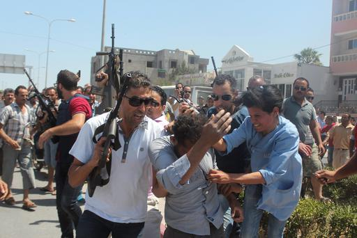 Tunisian police attempt to control the crowd while surrounding a man suspected to be involved in opening fire on tourists at a beachside hotel in Sousse