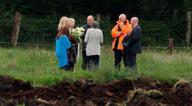 Local priest Father John O'Brien and Geoff Knupfer (wearing orange jacket), head of the investigation team for the Independent Commission for the Location of Victims' Remains (ICLVR), with members of Seamus Wright's family at the site in Coghalstown, Co Meath, where two bodies were discovered on a reclaimed bog where three of the IRA Disappeared are believed to be secretly buried. Niall Carson/PA Wire