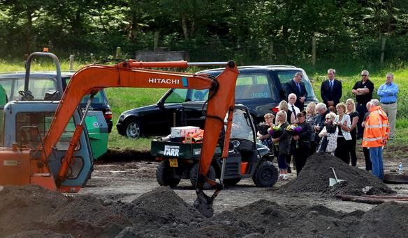 The families of Disappeared victims Seamus Wright and Kevin McKee take part in a ceremony where human remains were found in bogland, near the village of Wilkinstown in Ireland June 26, 2015. More than one body has been found during a search for IRA victims who have been missing since 1972, local media reported. REUTERS/Cathal McNaughton