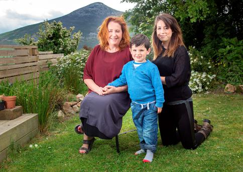 Happy family: Mary Coughlan pictured in her idyllic garden at the foot of the Sugar Loaf with her daughter Clare and grandson Felice. Photo: Tony Gavin
