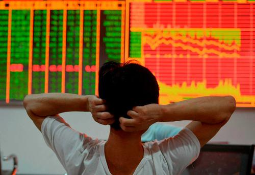 A stock investor gestures as he looks at a screen displaying share prices at a security firm in Hangzhou, east China's Zhejiang province. Photo: Getty Images