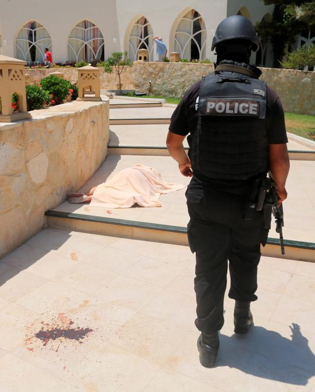 A police officer walks past a body covered near a Tunisian beach, in Sousse, Friday June 26, 2015. A young man unfurled an umbrella and pulled out a Kalashnikov, opening fire on European sunbathers in an attack that killed at least 28 people at a Tunisian beach resort one of three deadly attacks from Europe to the Middle East on Friday that followed a call to violence by Islamic State extremists. (Jawhara FM via AP)