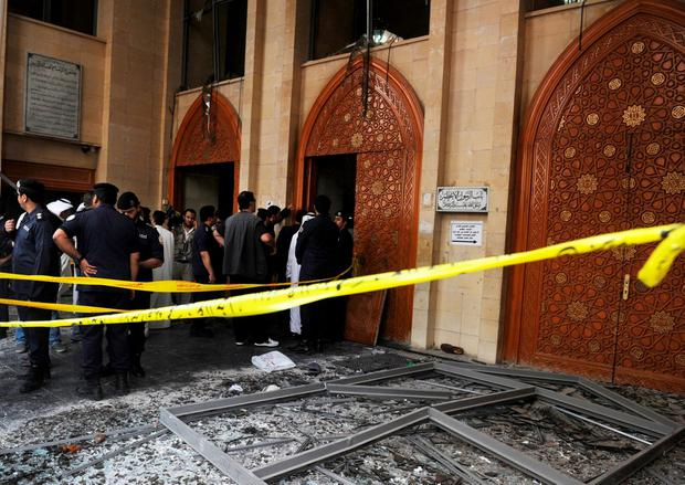 Security forces and officials gather at a Shiite mosque after a deadly blast claimed by the Islamic State group that struck worshippers attending Friday prayers in Kuwait City, Friday, June 26, 2015. (AP Photo)